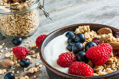 Bowl of oat granola with yogurt, fresh raspberries, blueberries and nuts. With cereals in a jar for healthy breakfast. close up Royalty Free Stock Photography