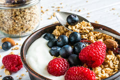 Bowl of oat granola with yogurt, fresh raspberries, blueberries and nuts. With cereals and spoon in a jar for healthy breakfast. close up Royalty Free Stock Photos