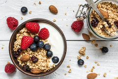 Bowl of oat granola with yogurt, fresh raspberries, blueberries and nuts. With jar of oats with a spoon on white wooden board for healthy breakfast. top view Stock Photo