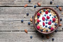 Bowl of oat granola with yogurt, fresh raspberries, blueberries and nuts. On rustic wooden board for healthy breakfast, top view with copy space Royalty Free Stock Images