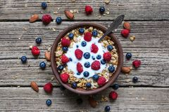 Bowl of oat granola with yogurt, fresh raspberries, blueberries and nuts with spoon. On rustic wooden board for healthy breakfast, top view Royalty Free Stock Photo