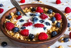Bowl of oat granola with yogurt, fresh raspberries, blueberries and nuts with spoon. On rustic wooden board for healthy breakfast, close up Stock Images