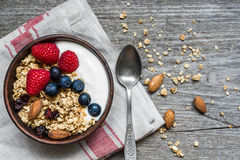 Bowl of oat granola with yogurt, fresh raspberries, blueberries and nuts. With a spoon on rustic wooden board for healthy breakfast. top view Royalty Free Stock Images