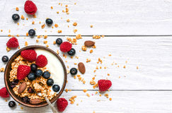 Bowl of oat granola with yogurt, fresh raspberries, blueberries and nuts. With spoon on white wooden board for healthy breakfast, top view Stock Images