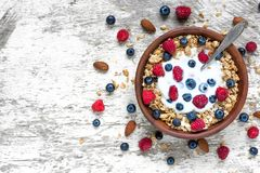 Bowl of oat granola with yogurt, fresh raspberries, blueberries and nuts with spoon on white wooden table. For healthy breakfast, top view with copy space Royalty Free Stock Photo