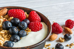 Bowl of oat granola with yogurt, fresh raspberries, blueberries and nuts. On white wooden board for healthy breakfast. close up Royalty Free Stock Photography