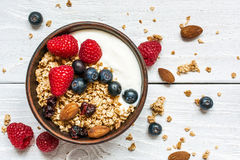 Bowl of oat granola with yogurt, fresh raspberries, blueberries. And nuts on white wooden board for healthy breakfast. top view Royalty Free Stock Image
