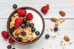 Bowl of oat granola with yogurt, fresh raspberries, blueberries and nuts. On white wooden board for healthy breakfast. top view Stock Photos
