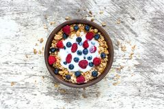 Bowl of oat granola with yogurt, fresh raspberries, blueberries and nuts on white wooden table. For healthy breakfast, top view Stock Images