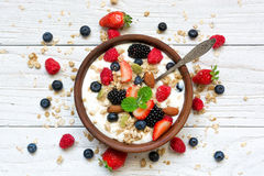 Bowl of oat granola with yogurt, fresh raspberries, blueberries, strawberries, blackberries and nuts with spoon. On white wooden board for healthy breakfast Stock Photos
