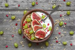Bowl of oat granola with yogurt, pomegranate seeds, figs, grape and nuts with a spoon Royalty Free Stock Photo