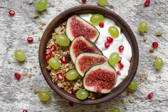Bowl of oat granola with yogurt, pomegranate seeds, figs, grape and nuts Stock Image