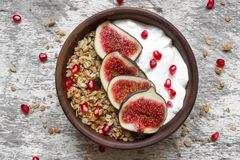 Bowl of oat granola with yogurt, pomegranate seeds, figs and nuts Stock Photos
