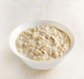 Bowl of oat porridge on wooden table Stock Photos