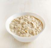 Bowl of oat porridge on wooden table Stock Photos