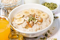 Bowl of oatmeal with banana, honey and nuts Royalty Free Stock Photography