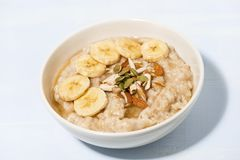 Bowl of oatmeal with banana, honey and nuts on table Royalty Free Stock Images