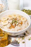 Bowl of oatmeal with banana, honey and nuts, vertical closeup Royalty Free Stock Photo