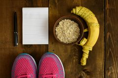 Bowl of oatmeal, Banana with yellow tape for measuring figure, empty notepad and trainers on dark wooden background. Top view, copy space Royalty Free Stock Photography