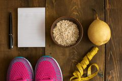 Bowl of oatmeal, Banana with yellow tape for measuring figure, empty notepad and trainers on dark wooden background. Top view, copy space Royalty Free Stock Photos