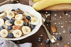 Bowl of Oatmeal Bananas, Pecans, honey and Blueberries royalty free stock image