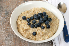 Bowl of Oatmeal with Blueberries. Blue-handled spoon on side with vintage white napkin Stock Photo