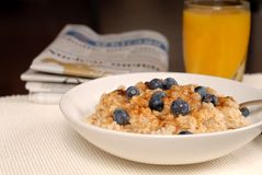Bowl of oatmeal with brown sugar, blueberries, orange juice Royalty Free Stock Photo