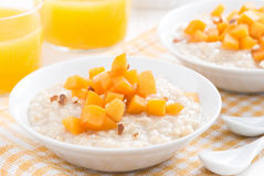 Bowl of oatmeal with fresh apricots and orange juice Stock Image