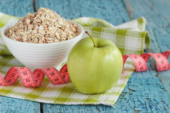 Bowl of oatmeal, green apple and tape measuring Royalty Free Stock Photos