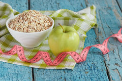 Bowl of oatmeal, green apple and tape measuring Stock Image
