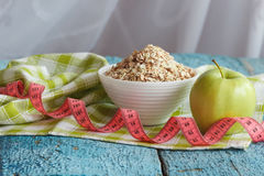 Bowl of oatmeal, green apple and tape measuring Royalty Free Stock Photo