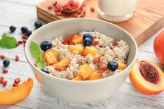 Bowl with oatmeal, peaches and berries. On table stock images