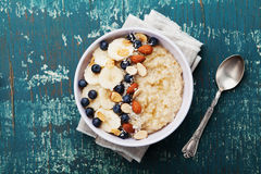 Bowl of oatmeal porridge with banana, blueberries, almonds, coconut and caramel sauce on teal rustic table,  top view, flat lay Royalty Free Stock Images