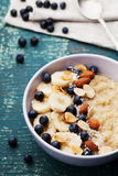 Bowl of oatmeal porridge with banana, blueberries, almonds, coconut and caramel sauce on teal vintage table, hot and healthy food royalty free stock photography