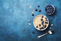 Bowl of oatmeal porridge with banana and blueberry on vintage table top view in flat lay style. Healthy breakfast and diet food. Royalty Free Stock Image