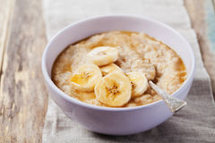 Bowl of oatmeal porridge with banana and caramel sauce on rustic table, hot and healthy breakfast Royalty Free Stock Image