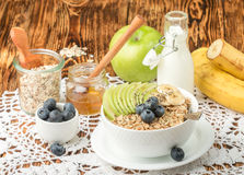 Bowl of oatmeal porridge with green Apple, banana, blueberries, honey and Chia seeds Stock Image
