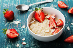 Bowl of oatmeal porridge with strawberry and almond flakes on vintage teal table. Hot and healthy breakfast and diet food. Bowl of oatmeal porridge with Royalty Free Stock Photo