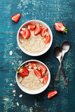 Bowl of oatmeal porridge with strawberry and almond flakes on wooden teal table top view in flat lay style. Healthy breakfast. Royalty Free Stock Image
