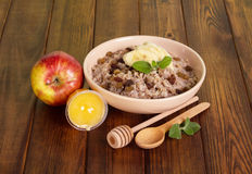 Bowl oatmeal with raisins, honey and apple on  dark tree. Royalty Free Stock Images