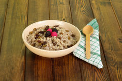 Bowl oatmeal with raisins, spoon, cotton cloth on dark wood. Stock Photos