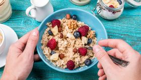 Bowl of oatmeal with raspberries and blueberries on a blue wooden table. Royalty Free Stock Image