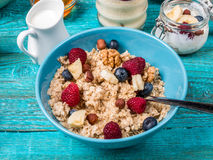Bowl of oatmeal with raspberries and blueberries on a blue wooden table. Stock Photography