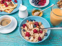 Bowl of oatmeal with raspberries and blueberries on a blue wooden table. Stock Images
