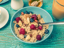 Bowl of oatmeal with raspberries and blueberries on a blue wooden table. Toned photo. Stock Photos