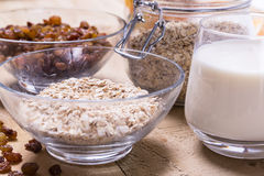 Bowl of oats. Raisins cup of milk on the wooden table Royalty Free Stock Photography