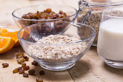 Bowl of oats. Raisins cup of milk on the wooden table Stock Photo