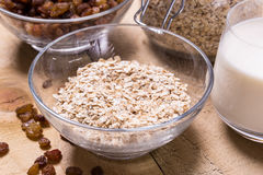 Bowl of oats. Raisins cup of milk on the wooden table Stock Image