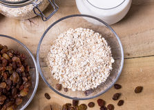 Bowl of oats. Raisins cup of milk on the wooden table Royalty Free Stock Photo