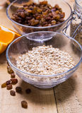 Bowl of oats. Raisins cup of milk on the wooden table Stock Photos